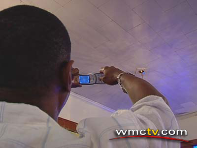 A church member frames the face of God in his cell phone